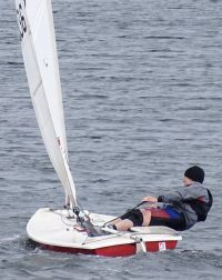 A sailor hiking hard in a Laser dinghy